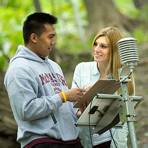 Image of McMaster Earth and Environmental Sciences students conducting experiment in outdoor setting with trees in background